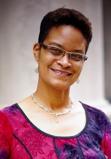 Image of a smiling Black woman with short hair and glasses facing the camera.